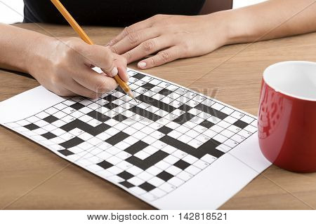 Solving crossword puzzle with yellow pencil.