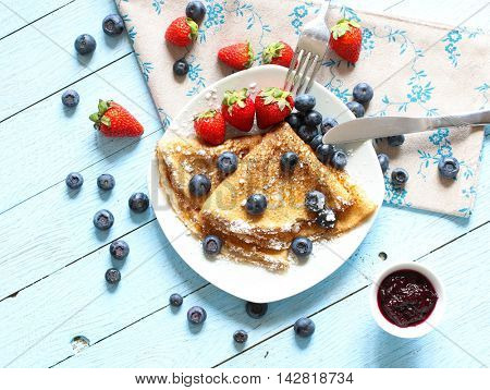 Delicious Crepes Breakfast with Dramatic light over a vintage wood background. An healthy meal of Pancakes with marmalede, blueberries and strawberries.
