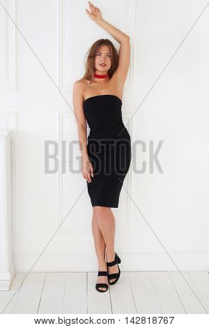 Well-graced European model in a black dress poses with her hand up. This attitude makes the photo especially hot