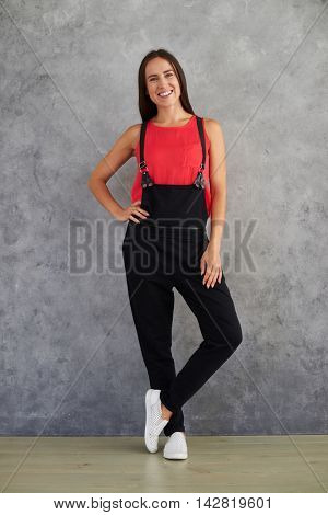Young fashion girl in black overalls posing isolated on gray background