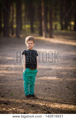 Disappointed upset little kid boy pinching his nose. close up outdoor. A cute boy in a green trousers and a grimace on his face standing in a pine forest. Sunny day.
