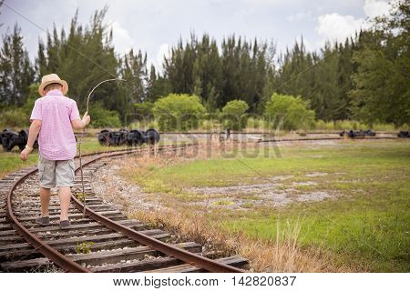 Cute kid boy in straw hat goes on rails back to a camera in field in the summer. Child walking along old railroad.