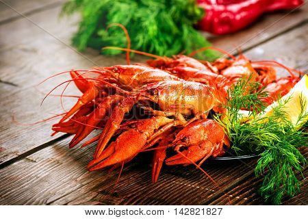 Crawfish. Red boiled crawfishes on a wooden table in rustic style, close-up, selective focus. Lobster closeup