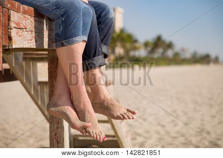 Closeup of man's and woman's feet. People sitting on the wooden deck on the beach. Couple enjoying summer day at the beach. Vacation mood.