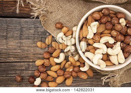 Almonds, Cashew And Hazelnuts In Ceramic Bowl On A Rustic Wooden Background. Top View. Healthy Conce