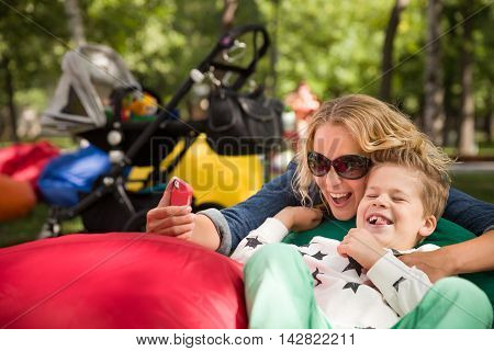 Portrait of young blond mother with cute kid boy smiling and taking selfie in the park on a sunny day. Family picture with smartphone. Happy mom and child taking picture of themselves. Lifestyle image