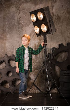 Cute boy in a plaid shirt fixing lights in a photo studio. Lighting correction. Young attractive photographer changing light force and direction. Gears background. Child before photoshooting.