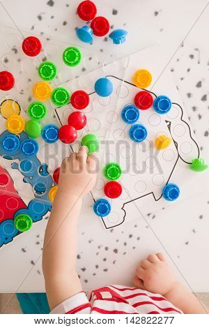 Closeup of child's hand taking bright mosaic parts. Playing and learning colors at home. Toddler boy playing with colorful constructor details. Top view. Activities with children