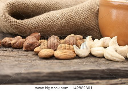Almonds, Cashew And Hazelnuts On A Rustic Wooden Board. Healthy Concept. Soft Focus.