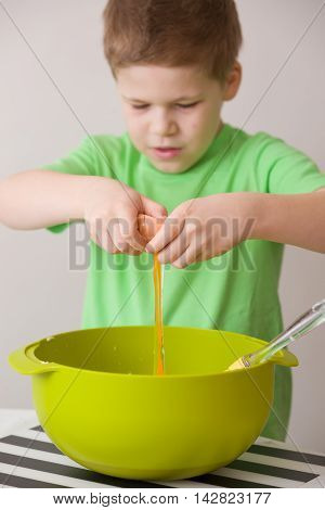 Cute little kid boy breaking an egg for the cupcake dough. Child in green t-shirt cooking in the kitchen. Indoors on the neutral background. Learning to cook and bake with ingredients.