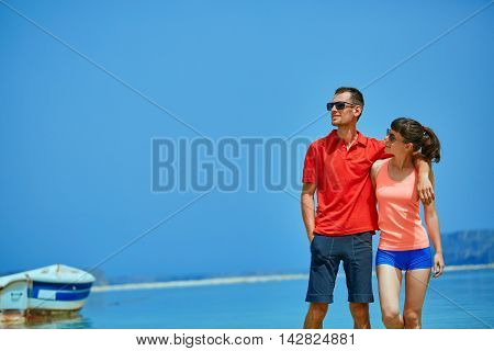 couple standing in the sea near the boat. They hold each other's hands