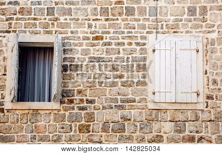 old wall with open and closed wooden windows