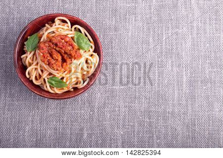 Top view of a gray mat with a small portion of cooked spaghetti in a small wooden bowl of brown