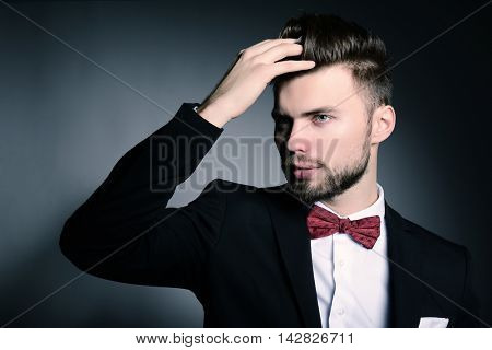 Portrait of handsome stylish man in elegant black suit and red bow-tie over gray background, image toned
