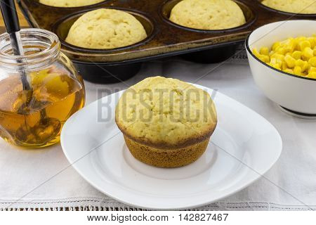 Corn muffin in plate with muffins in pan syrup and corn in a bowl on white cloth