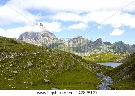 Midi D'ossau Peak Behind Another Mountain And A Lake In Ayous Lakes, France