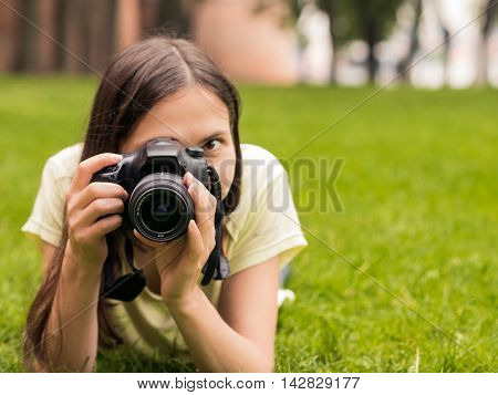 Young woman photographer with camera lie down on grass with copyspace