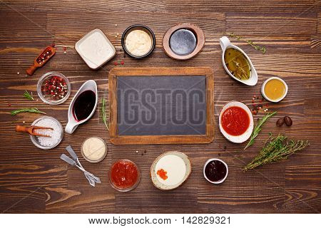 Different Sauces and Seasonings and Black Chalk Board. Food background with copy space. Top view