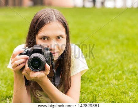 Young woman photographer with camera lie down on grass with copyspace. Focus at camera. Shallow DOF