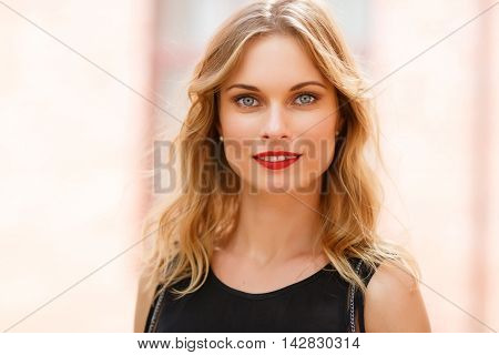 Outdoors closeup portrait of blonde woman with grey eyes and natural makeup