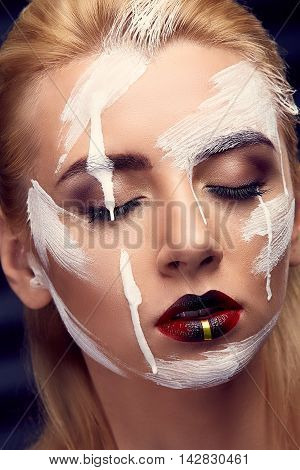 Fashion blonde model portrait with beautiful makeup. Professional makeup, false eyelashes and red lips. Face covered with white paint stripes.