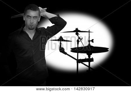 Young bearded drummer holding drum sticks. Black and white photography