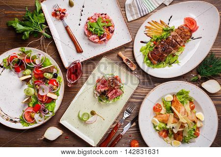 Different salads on wooden table, top view. Vegetable salad, Salad with smoked duck, Grilled chicken Caesar salad.