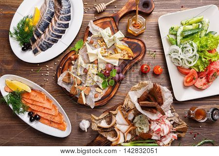 Various delicacies on the table. Cheese platter, sliced smoked salmon, mackerel, bacon, and vegetable salad. Food background, Top view