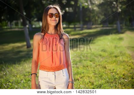 beautiful hipster girl in sunglasses smiling and looking at the camera