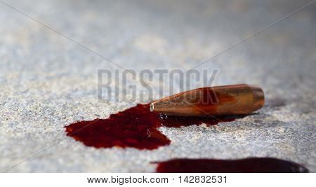 Copper plated rifle bullet on concrete with a lot of blood