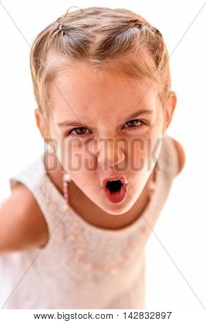 Portrait of a little girl with braids screaming. Child with braided hair is looking at the camera yelling.