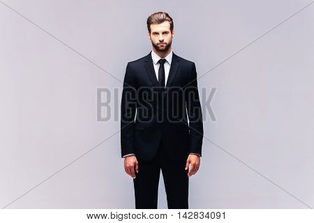 Young and confident. Studio shot of handsome young man in full suit looking at camera