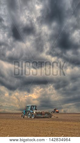 Tractor sowing the field on a stormy day