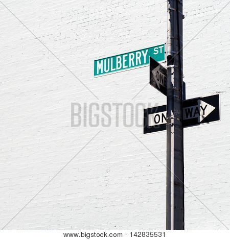 Mulberry Street and two One Way signs on a pole against a white brick wall in Little Italy, New York City, USA.