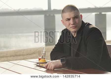 Young handsome man sitting in an outdoor cafe by the river drinking tea holding a tablet computer and surfing the net on a sunny autumn day