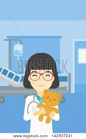 Young asian female pediatrician doctor holding a teddy bear. Professional pediatrician doctor with a teddy bear in the hospital room. Vector flat design illustration. Vertical layout.