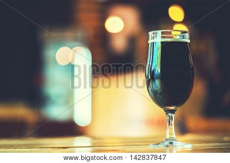 A Fresh Glass Of Cold Dark Beer On The Wooden Bar Counter In Pub With Free Space For Your Text. Beau