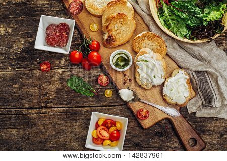 Appetizer Bruschetta with soft cheese, tomatoes, sausage and herbs.