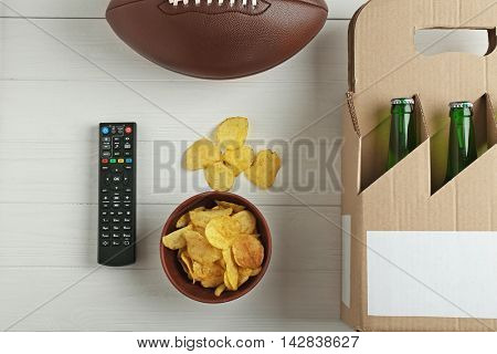 TV remote control with ball, snack and beer on white background