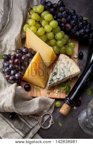 Assortment of various types of cheese on wooden board. Selective focus