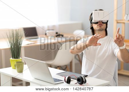Lost in the world. Puzzled young man sitting at the table and using virtual reality device