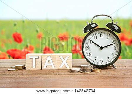 Word tax on wooden blocks with stacked coins and alarm clock. Financial concept.