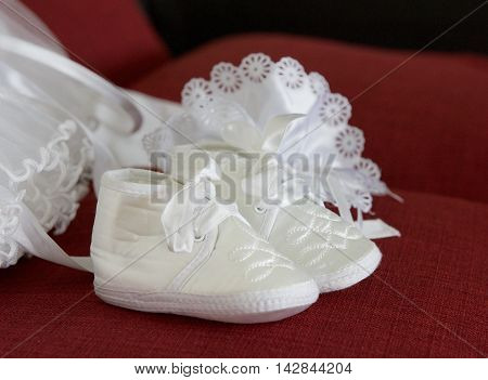Baptism baby shoes on red blurry noisy background, catholic family event - baptism, and clothes ready for baptism