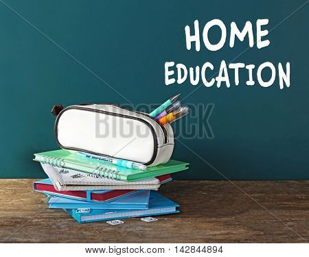 Home education concept. Pencil case with various stationery on table, on blackboard background