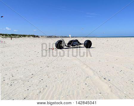 Kite buggy on beach with blue sky