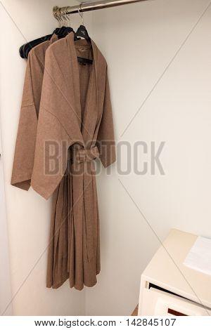 Bathrobe for couple hang in wardrobe in hotel