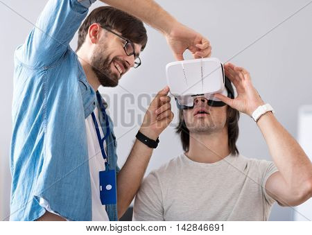 Involved in experiment. Positive delighted smiling colleagues working on the project while testing virtual reality glasses