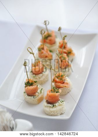Canapes with salmon, batter, cream cheese and fennel on white plate