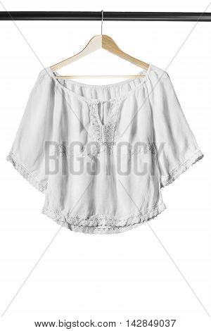 White ethnic blouse on wooden clothes rack isolated over white