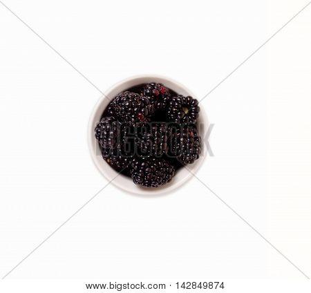 Black berry on white background. Blackberries in ceramic bowl.